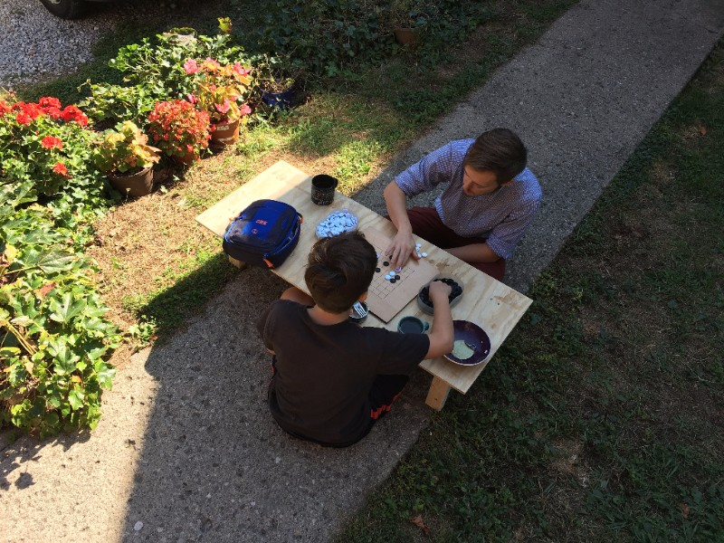 """Devin and Jeremiah playing """"Go"""" in the garden on a table that Jeremiah built during Basics of Carpentry."""