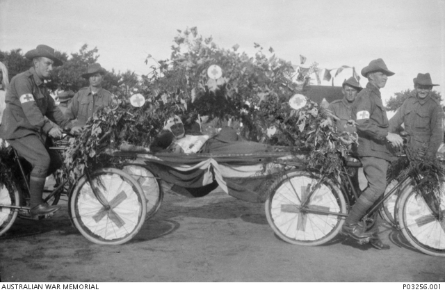 c 1917; an unidentified wounded soldier in a makeshift ambulance formed by four bicycles