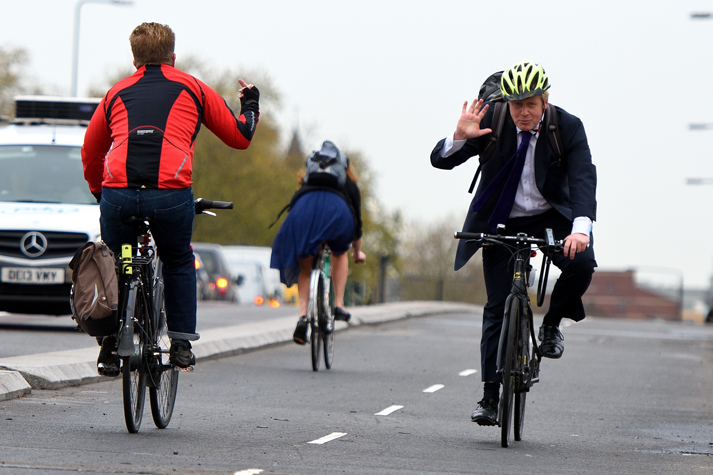 A cyclist gives the traditional wave to a passing politician.