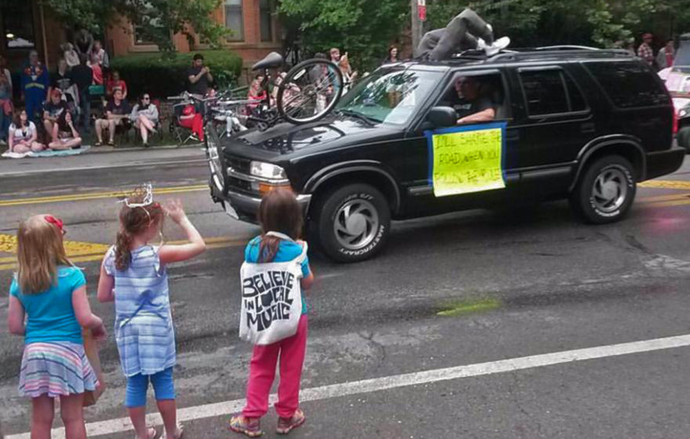 """The sign says """"I'll share the road when you follow the rules""""; there's a crumpled bike embedded in the car, and a dummy dressed as a cyclist hanging through the sunroof. The other dummy is driving."""