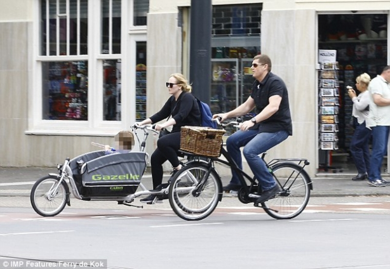 Adele ferries her kid around in a cargo bike ... accompanied by bodyguard. Sprocketman missed his calling there ...