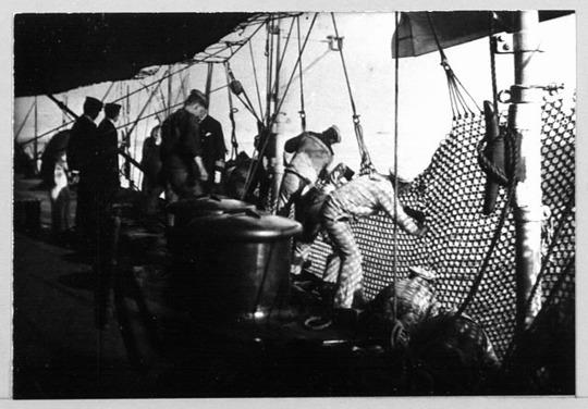 HMS Jupiter (1895) hoisting in torpedo netting.