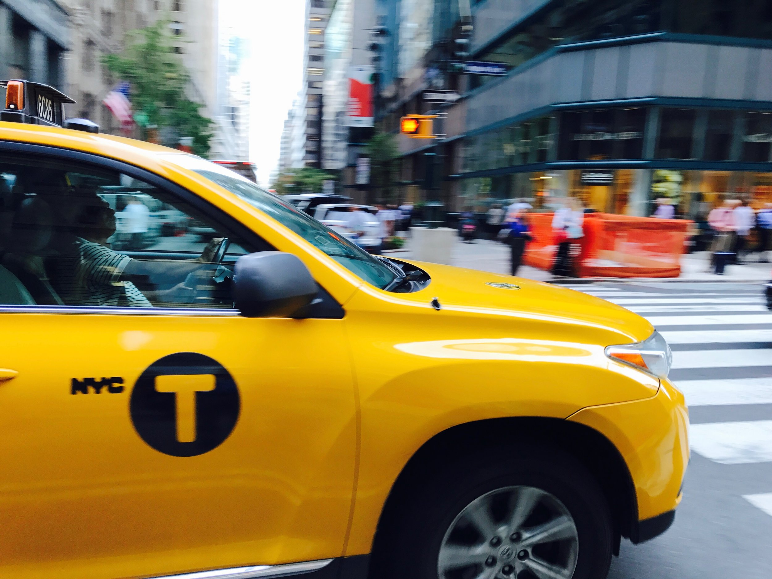 Taxi on Lexington Avenue  On Lexington Avenue, I'll often pull out my phone and try to grab panning shots of cars going by. So as the car comes up, I'll hit the shutter and attempt to move the phone in the same direction as the car while it passes. Hence the blurry background and less blurry car.