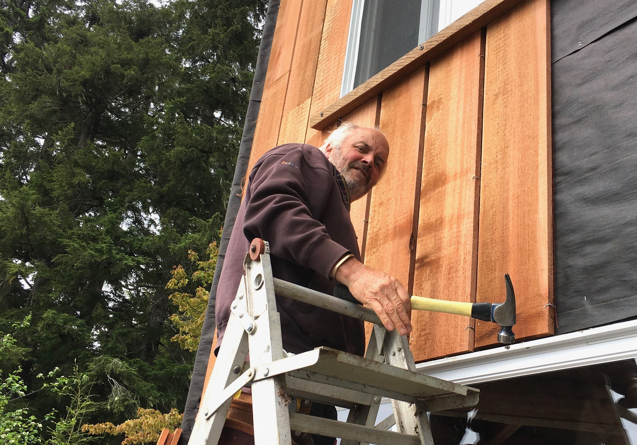 Phil installing new siding.