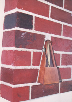 TIME IN STONE   Fiber board, brick wall, and a found Seth Thomas metronome.