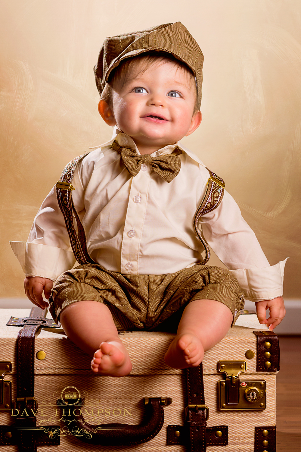 The old-time suit just adds to this stylized toddler portrait.  The suitcase prop adds interest and a bit of fun to this family photo.