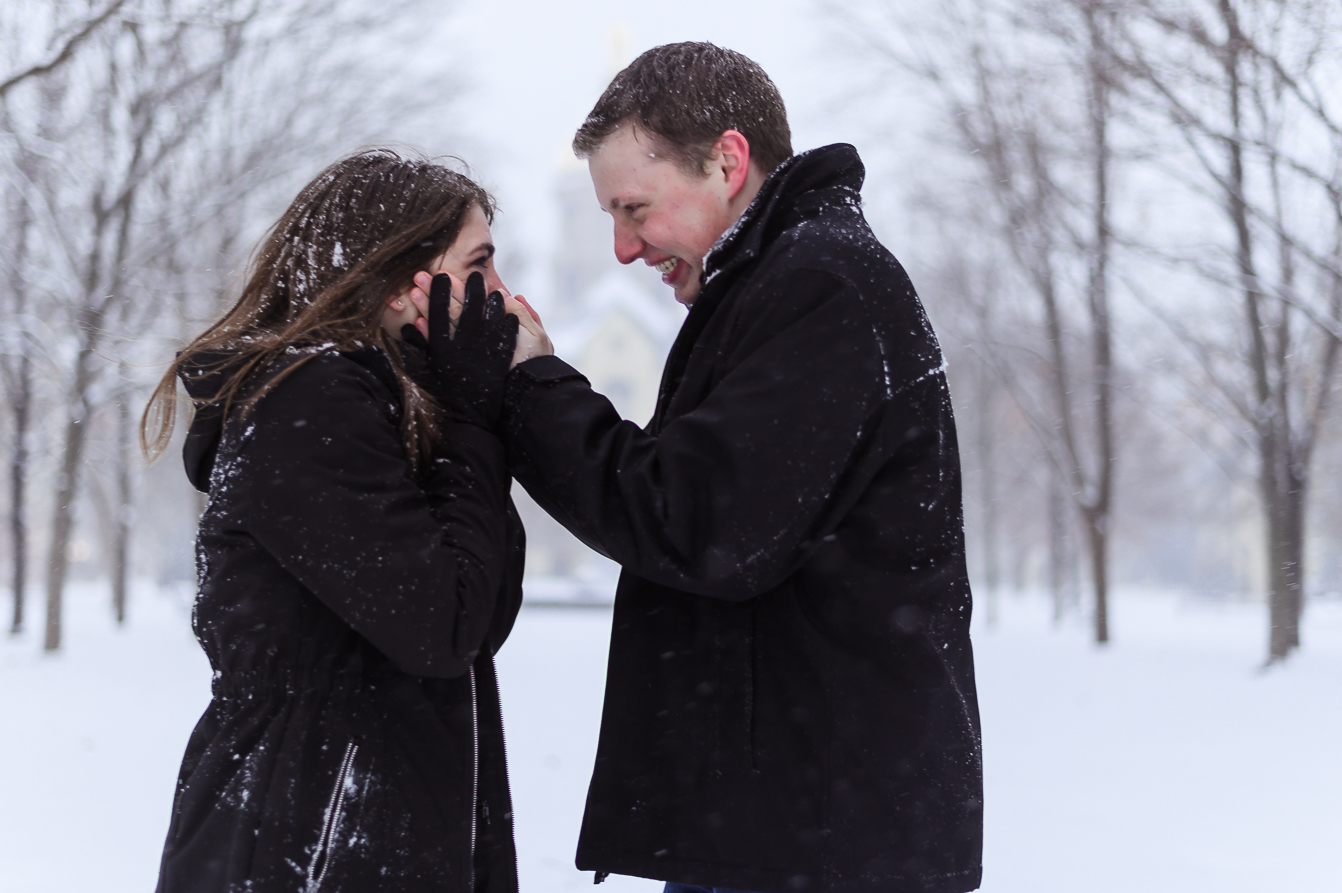 A cute couple in the middle of a snowball fight for the camera for enagement memories.