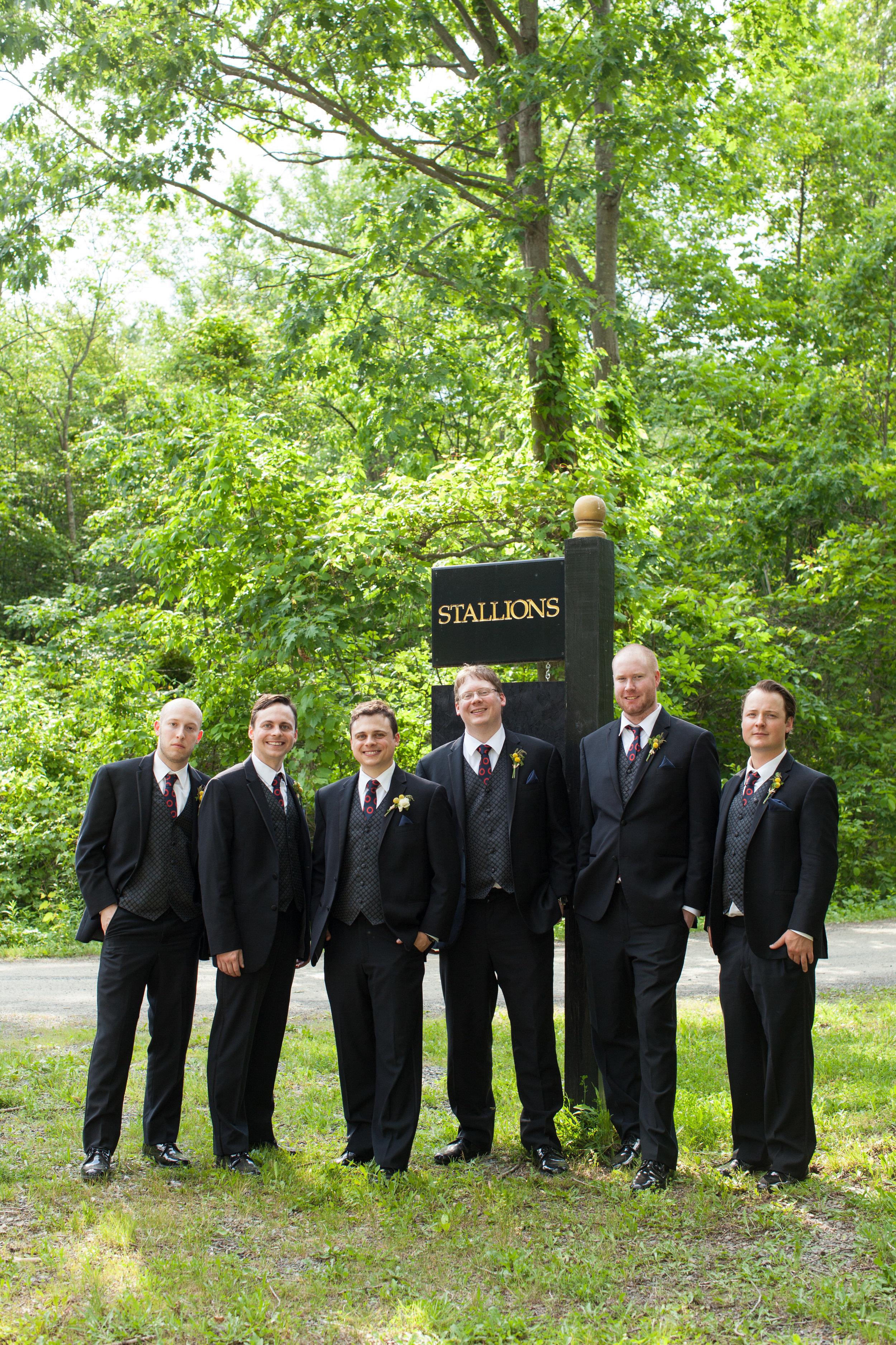 Groomsmen at the stallion sign.jpg