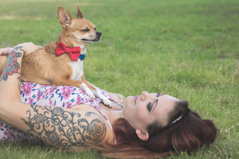 owner laying on ground in grass with dog sitting on chest