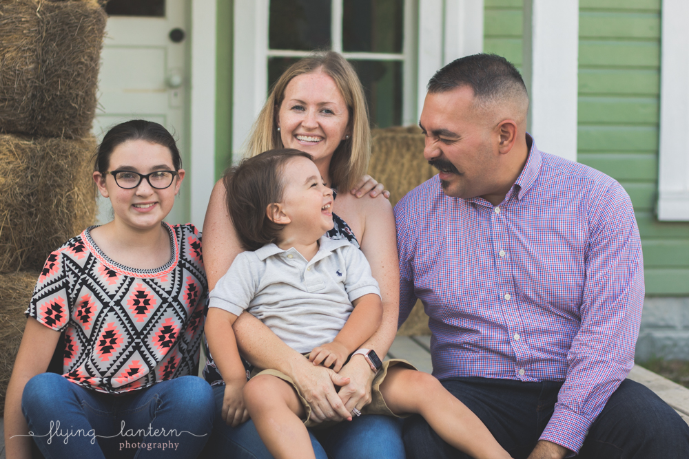 family of four portrait dad smiling at son