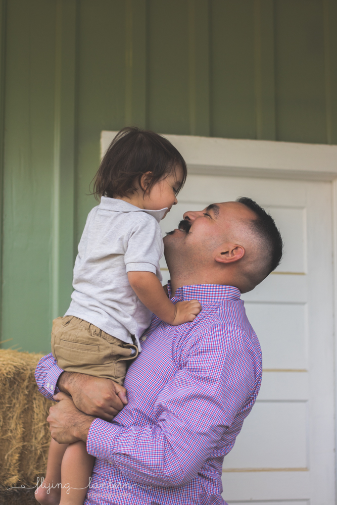 dad holding son looking up and smiling