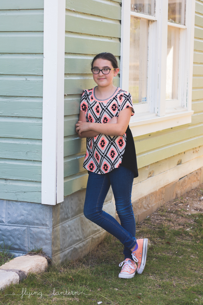 twelve year old girl leaning against side of house