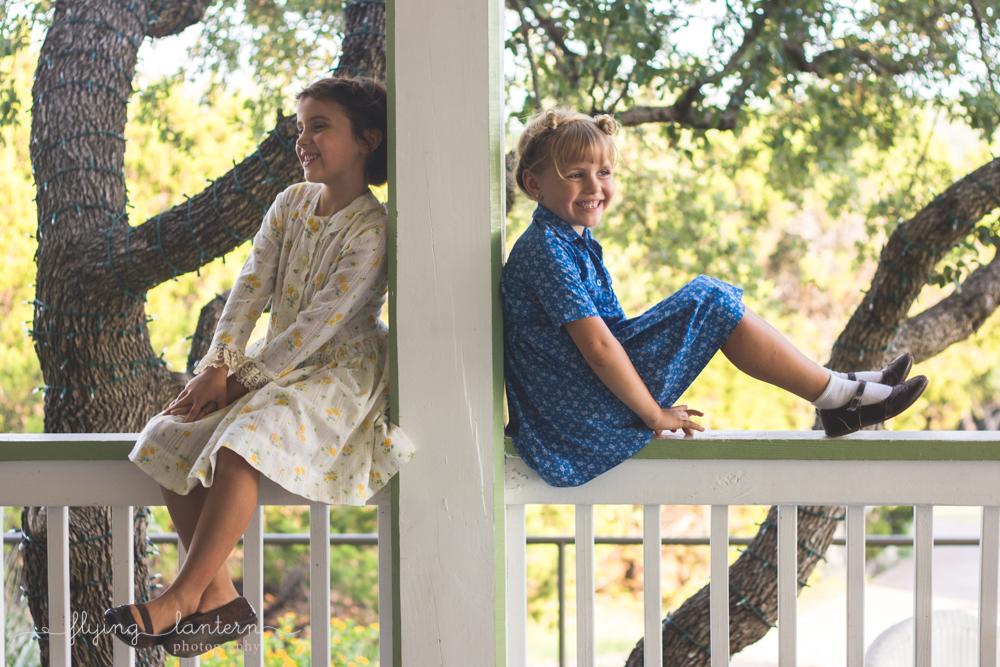 little girls sitting on deck bannister