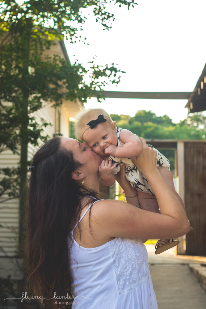 mother holding baby and kissing cheek
