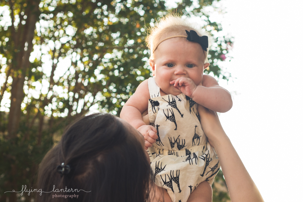 little baby being held up looking down
