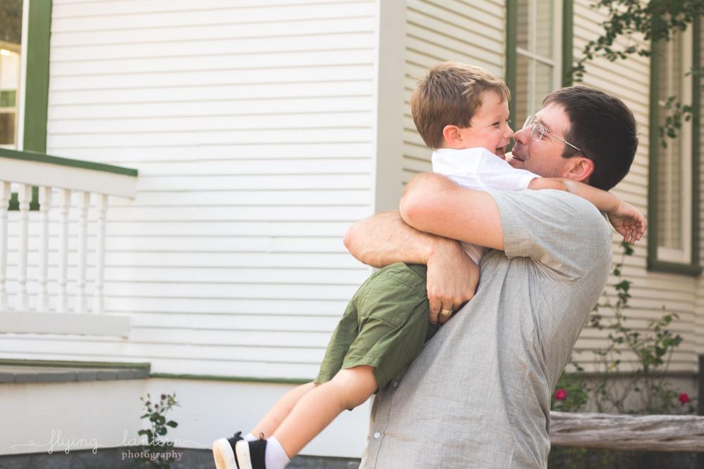 father holding onto son with bear hug
