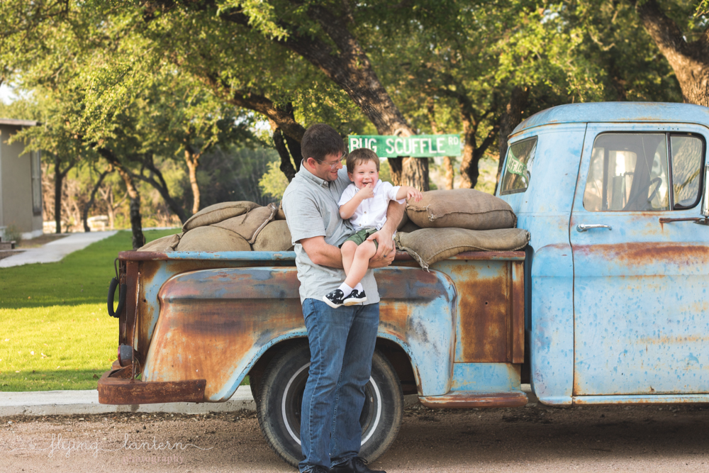 father and son standing in front of blue vintage truck