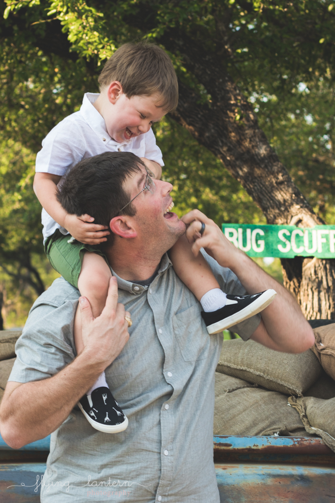 son on father's shoulder looking at each other
