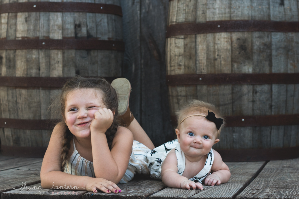daughters laying on bellies with barrels behind them