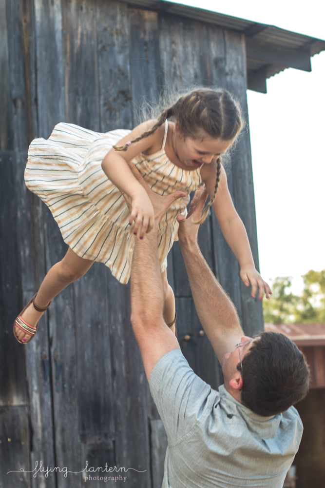 father throwing daughter into air