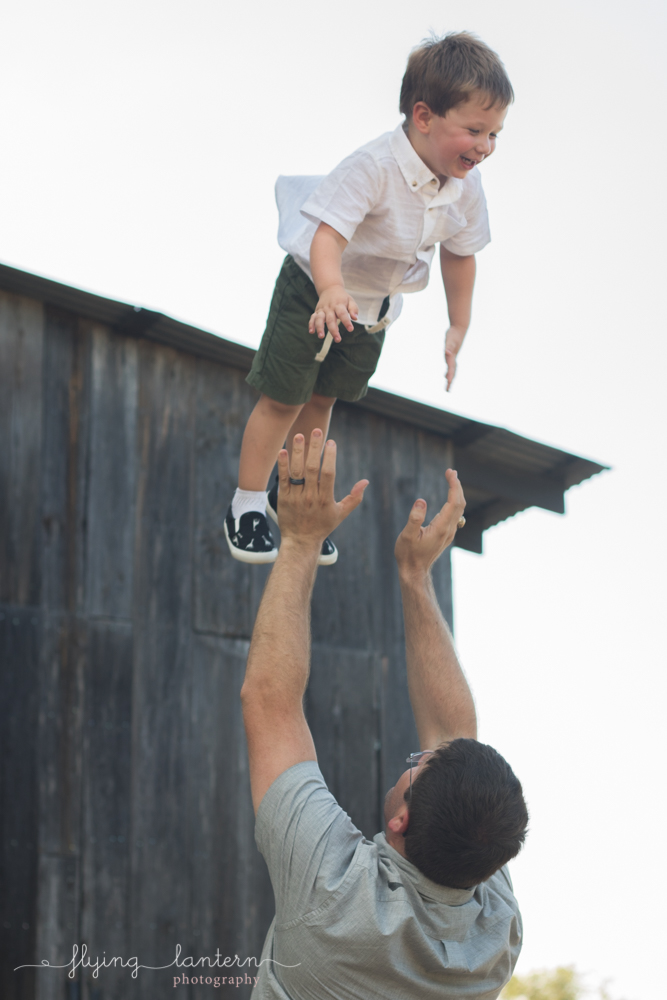 father throwing son into air