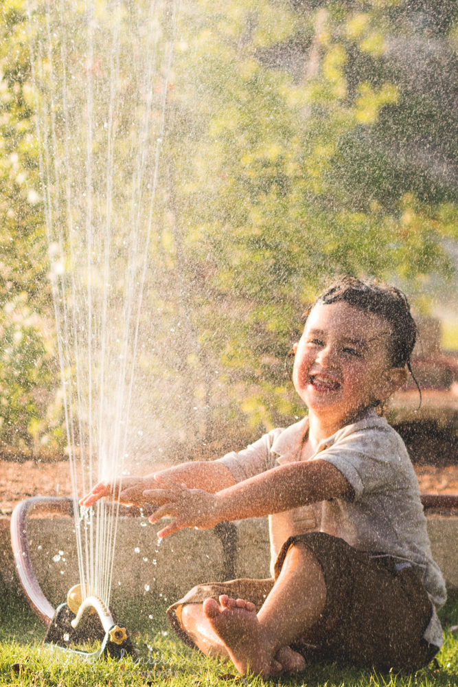 little boy playing in sprinkler and smiling