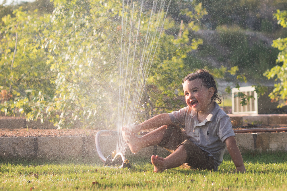 two year old boy playing in sprinkler with toes