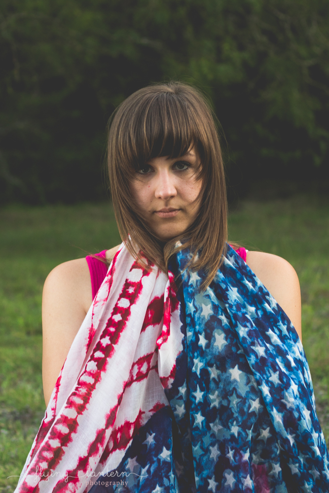 girl giving serious look at camera with flag up to chin draping down