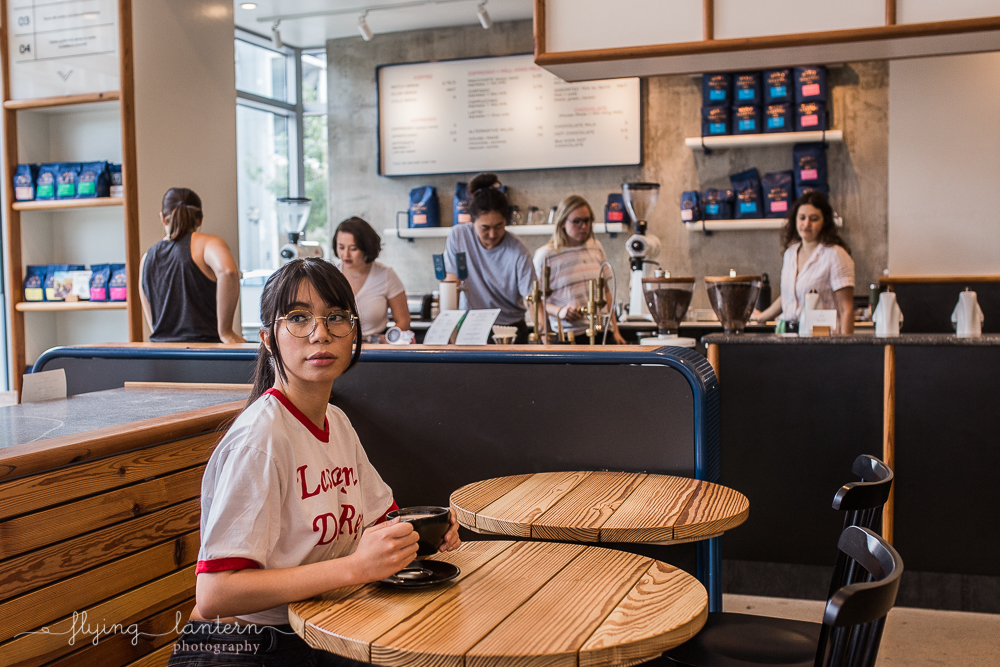 girl portrait in austin, texas at merit coffee shop holding coffee mug photo by erin reas of flying lantern photography