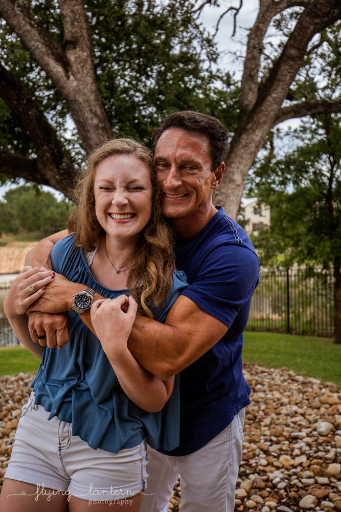 Father daughter smiling and hugging during extended family portrait session in Kingsland, TX. Photo by Erin Reas of Flying Lantern Photography