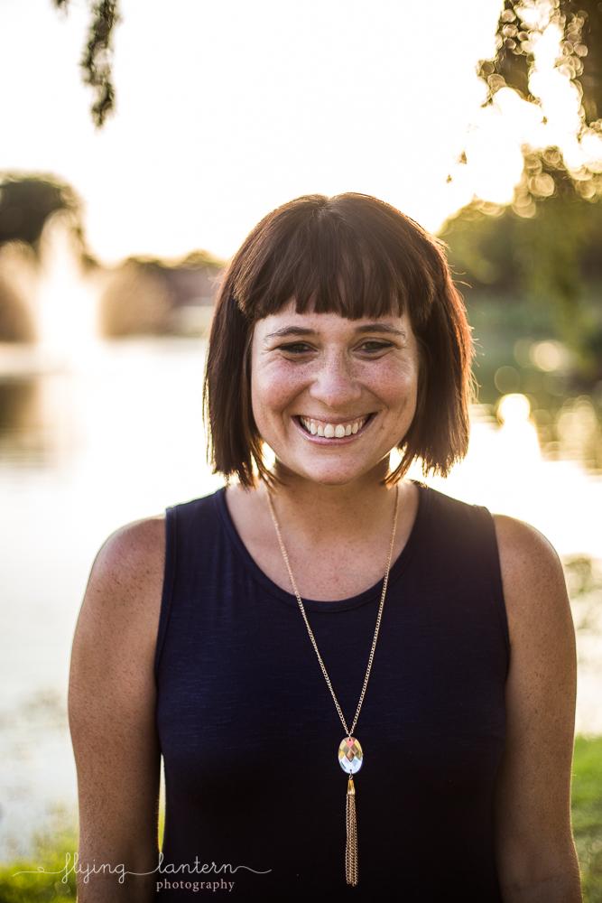 Austin blogger at mueller lake park headshot wearing navy dress and pendant necklace