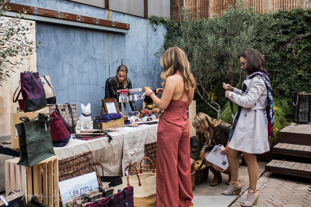 Girls looking at handmade goods at Ubuntu Life gala at the Pershing. Event Photography by Erin Reas of Flying Lantern Photography