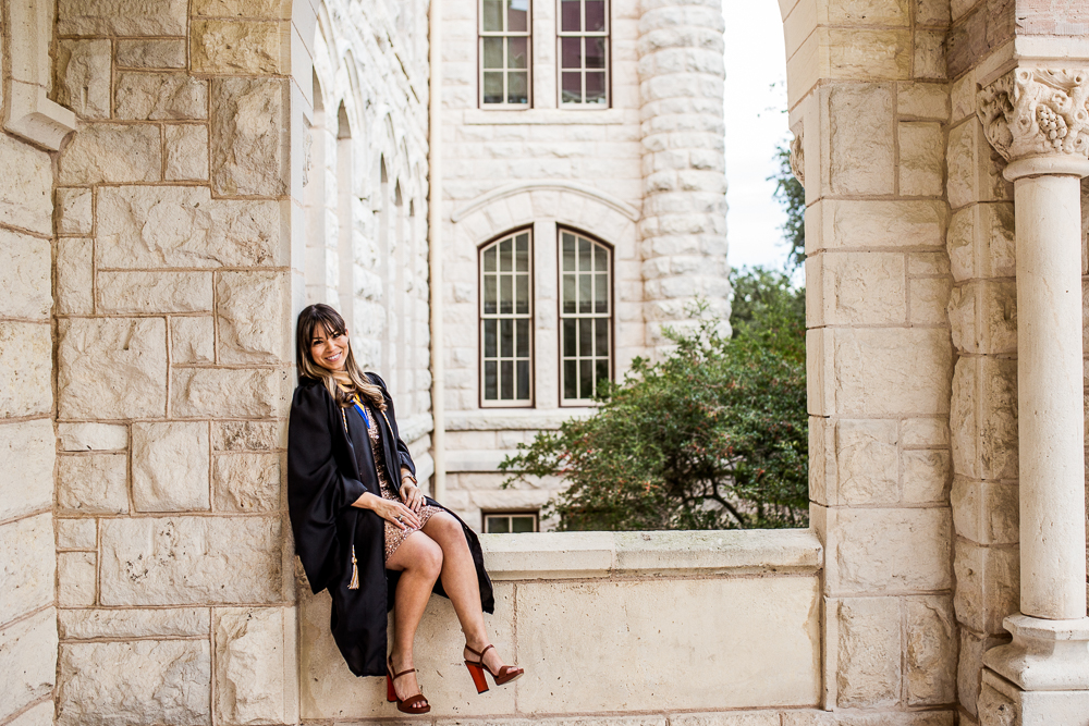 Graduate student at St. Edward's University in Austin, TX posing at main building ledge. Senior portrait by Erin Reas of Flying Lantern Photography.