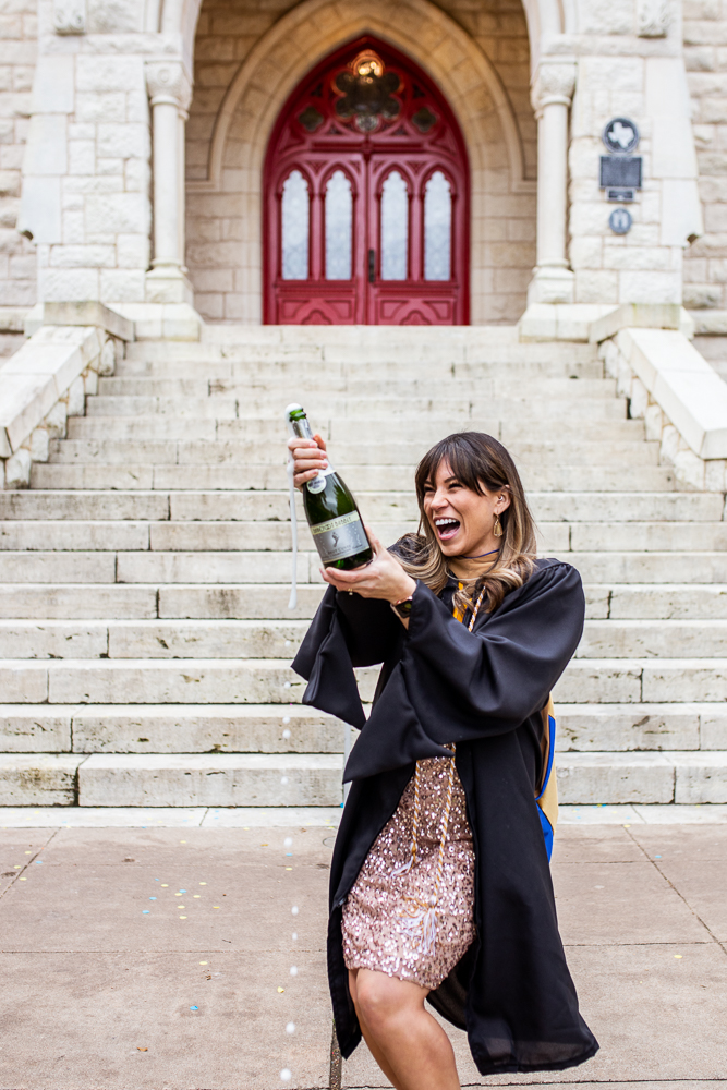 Graduate at St. Edward's University standing in front of Main Building popping champagne bottle and laughing. Senior portraits by Erin Reas of Flying Lantern Photography.