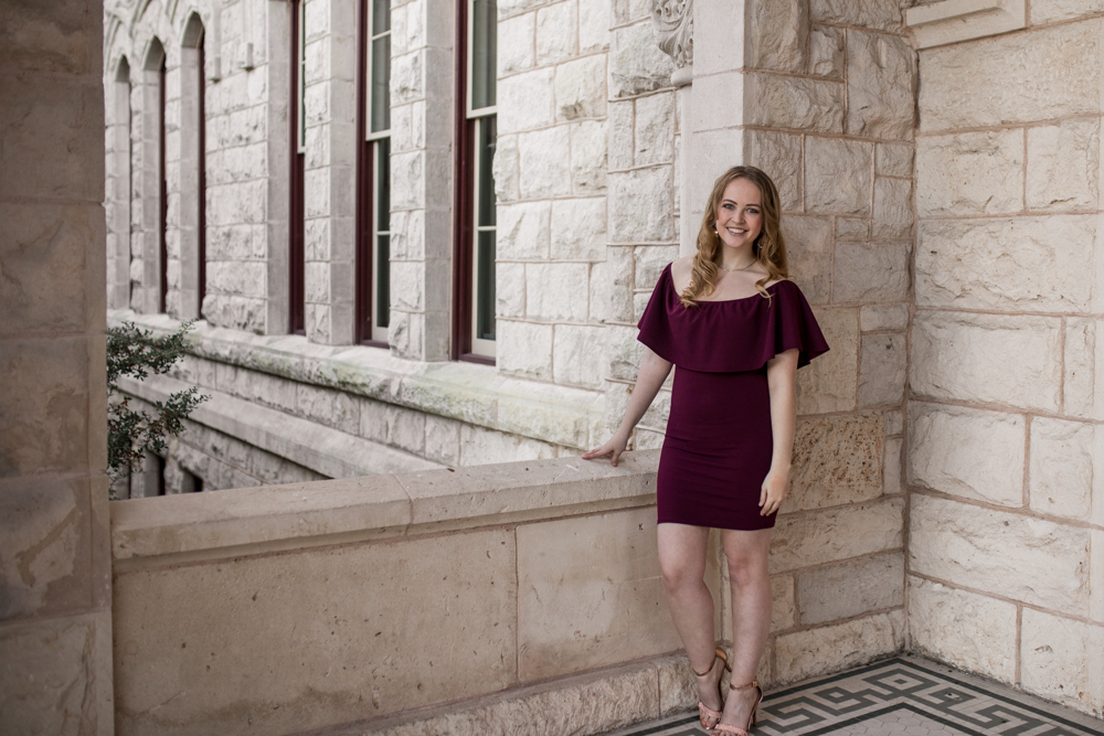 Senior portrait of girl at St. Edward's University at Main Building wearing purple dress. Photo by Erin Reas Austin, TX photographer