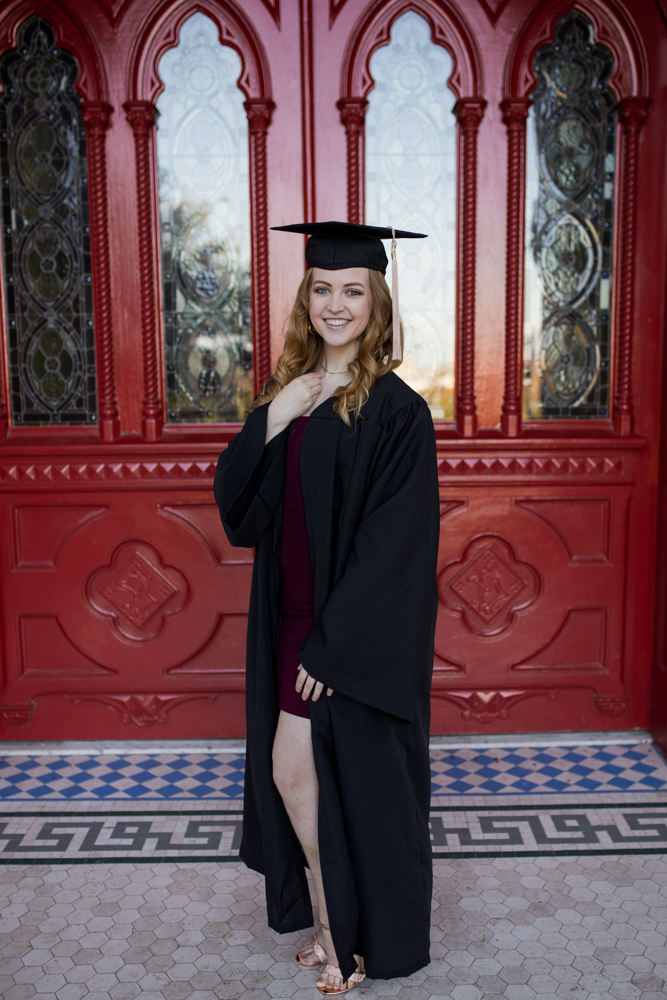Senior portrait of girl at St. Edward's University in front of red doors wearing purple dress and cap and gown. Photo by Erin Reas Austin, TX photographer