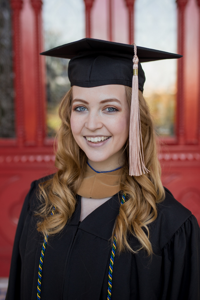Senior portrait of girl at St. Edward's University in front of red doors wearing graduation cap and gown. Photo by Erin Reas Austin, TX photographer