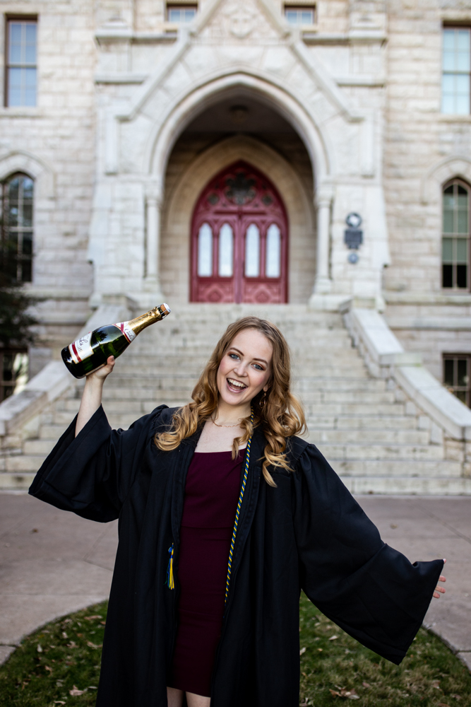 Senior portrait of girl at St. Edward's University in front of main building popping champagne bottle. Photo by Erin Reas Austin, TX photographer