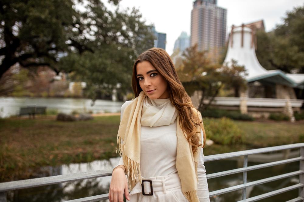 Lifestyle senior portrait at Auditorium Shores in Austin, Texas. Girl wearing white sweater and cream scarf. Photo by Erin Reas Austin area photographer