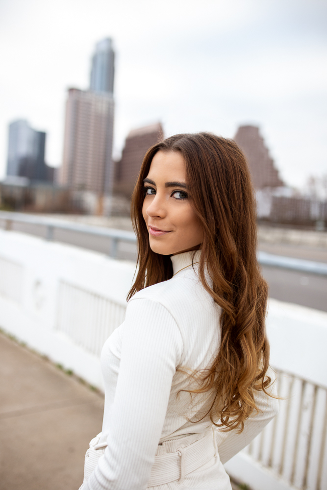 Austin lifestyle senior portrait session on S. 1st Street Bridge in Austin, TX. College graduate walking and looking back over shoulder. Photo by Erin Reas senior photographer
