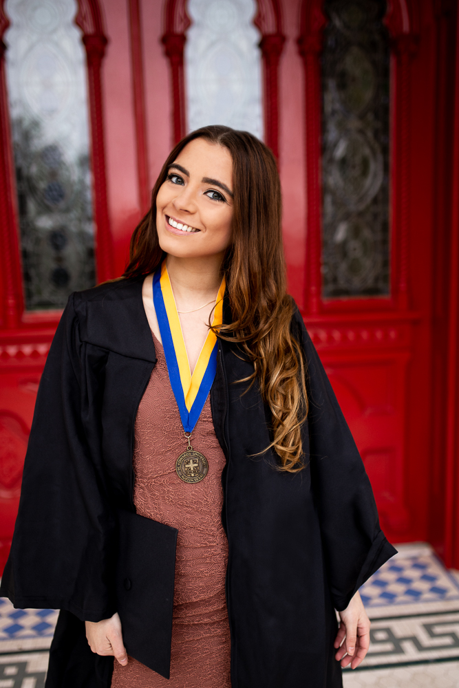 College graduate senior photo session at St. Edward's University in front of red doors. Graduate wearing cap and gown. Photo by Erin Reas senior photographer in Austin, TX