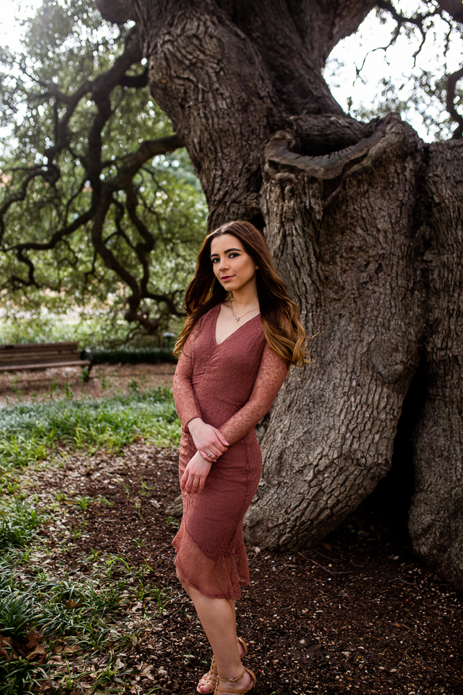 Senior photo session at St. Edward's University standing in front of Sorin Oak wearing rust colored lace dress. Photo by Erin Reas senior photographer in Austin, TX