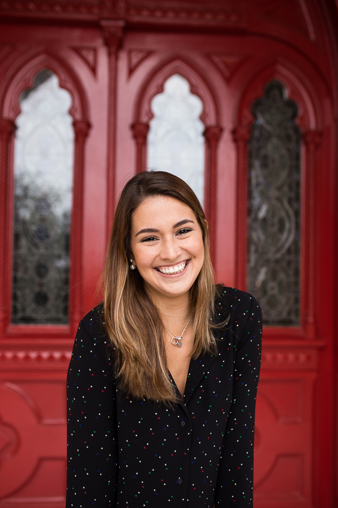 College graduate standing in front of red doors at St. Edward's University in Austin, TX. Senior photography by Erin Reas.