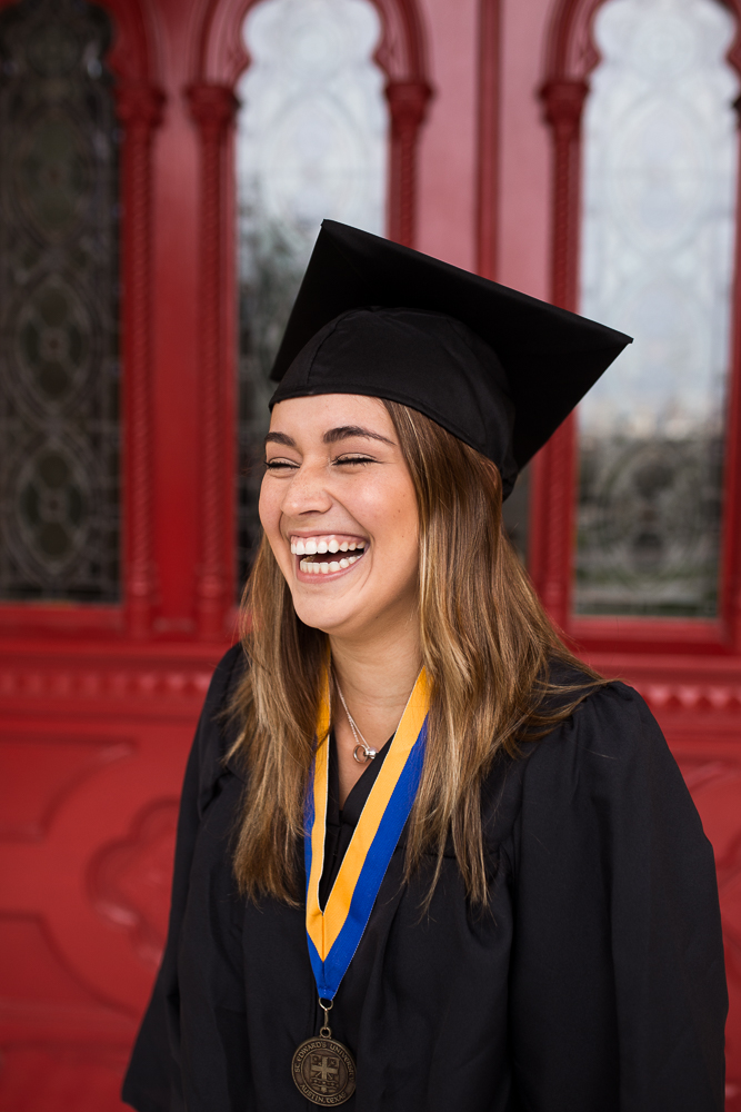 College graduate standing in front of red doors at St. Edward's University in Austin, TX wearing cap and gown and laughing. Senior photography by Erin Reas.