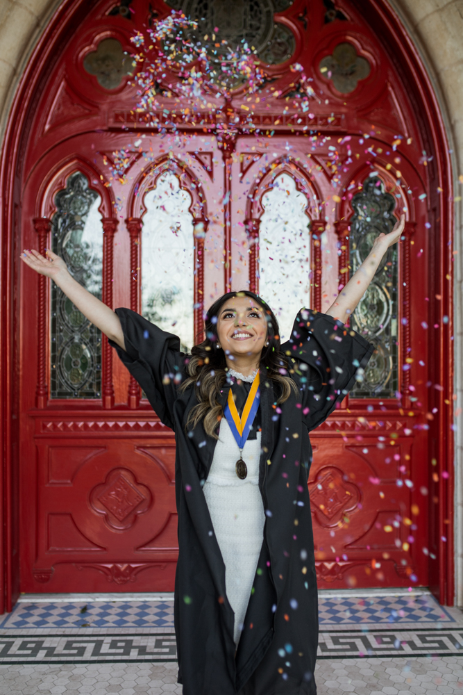 female college graduate standing in front of red doors at st. edward's university throwing confetti