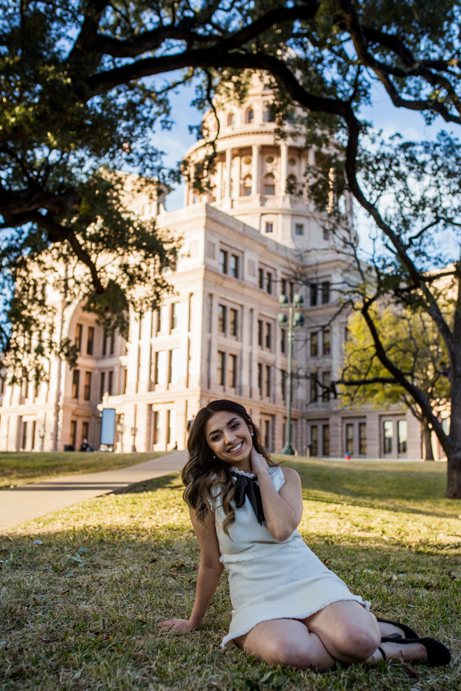 female college graduate sitting on lawn of texas state capitol building