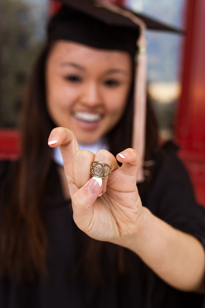 Female graduate showing off college class ring in front of red doors at St. Edward's University. Photo by Erin Reas local senior photographer