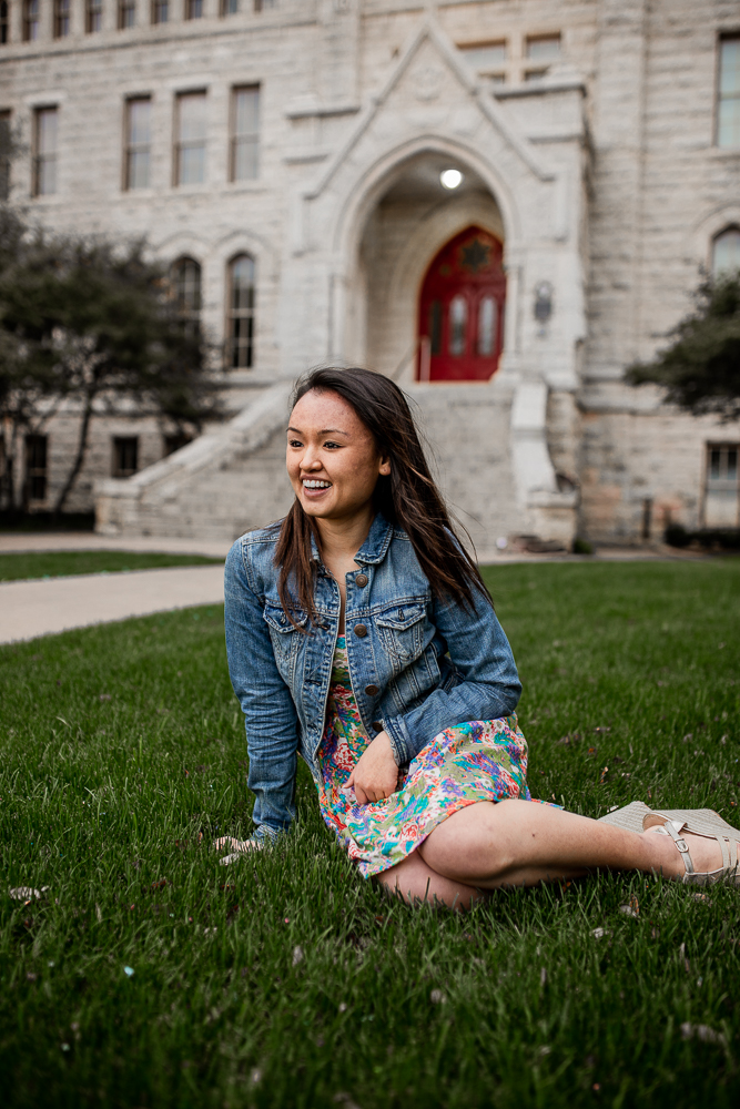 College graduate sitting on grass in front of Main Building at St. Edward's University wearing floral skirt and blue jean jacket. Photo by Erin Reas local Austin, TX senior photographer