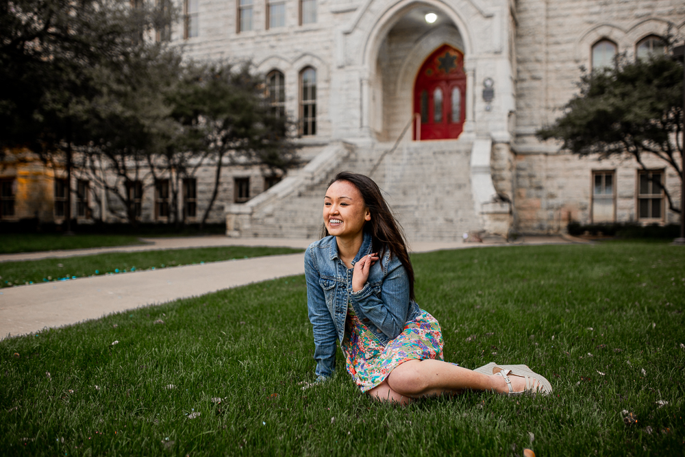Lifestyle portrait of college graduate sitting on grass and laughing wearing jean jacket and floral dress. Photo by Erin Reas local Austin, TX senior photographer.