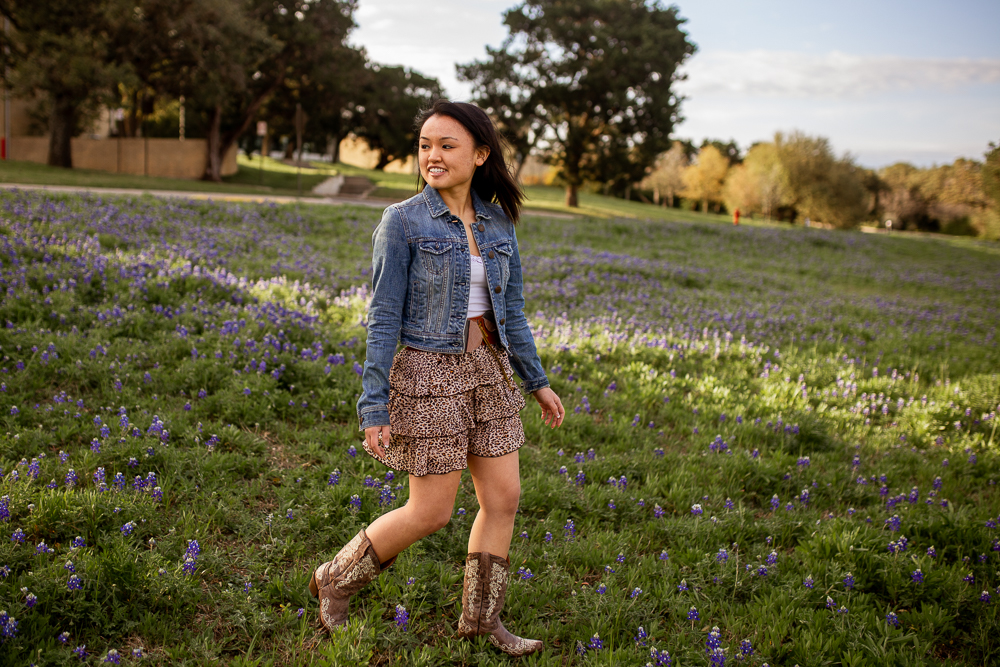 Female lifestyle portrait walking through bluebonnet field at St. Edward's University. Photo by Erin Reas senior photographer in Austin, Texas.